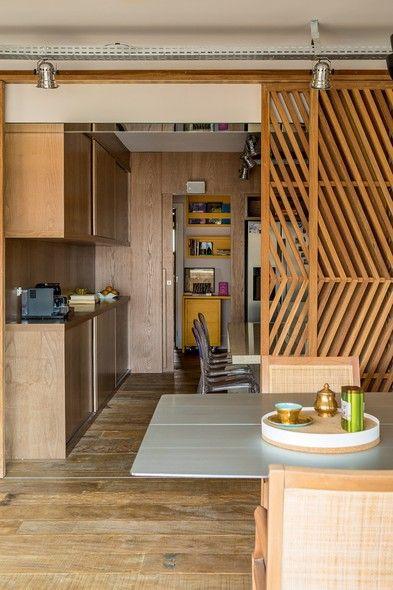 Executados pela Girante Móveis, armários de cappuccino e paredes revestidas dessa mesma madeira composta marcam o ambiente, com balcão de granito e cadeiras da Tok & Stok. Ao fundo, no corredor, fica o escritório com mobiliário amarelo feito sob medida