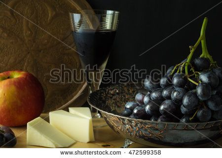 Antique fruit bowl with cluster of grapes, apple with pieces vegan cheese and a…