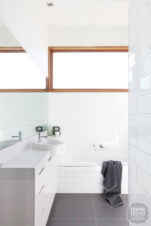 In the bathroom, a light and bright scheme is underpinned by glossy white wall tiles and large-format charcoal floor tiles.