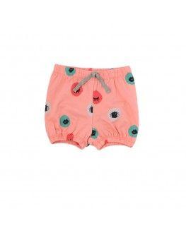 Auf dem pfirsich-farbenen Untergrund der Shorts von Iglo+Indi sind bunte Kreise mit Augen und Mündern verteilt.