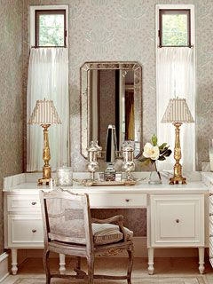 Silver-leafed wallpaper provides the basis for the colors and finishes in this ladies dressing area. Silver polished accessories brighten up a cream-colored vanity, and an antique French chair with a brown and gold distressed frame, is the perfect equalizer between the two tones.
