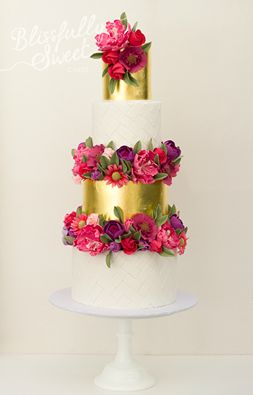 Loving the contrast between the gold layers and pink and purple flowers on this floral, romantic, and elegant wedding cake!