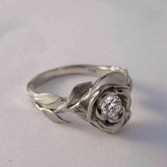 A handmade 14k white gold ring showing a large rose set with a beautiful 0.3ct clear diamond.  The rose is surrounded by a composition of leaves