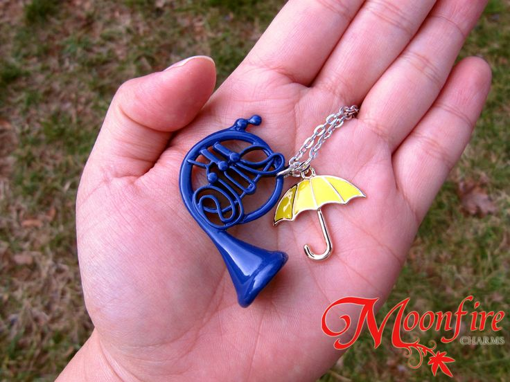 This necklace features the iconic blue French Horn and yellow umbrella, as seen in HIMYM. The silver and enamel-plated French Horn charm measures 4 cm by 3 cm. The gold and enamel-plated umbrella char