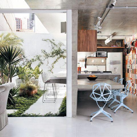 Casa 2. Um vistoso painel de ladrilhos hidráulicos (Dalle Piagge) forra a parede da cozinha. Ao redor da bancada de concreto, cadeiras azuis de metal (A Lot Of). O piso é de granilite polido branco.