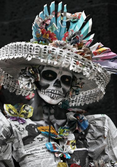 A woman dressed as the iconic Mexican 'Catrina' poses for photographers as she gathers with other women in costume in an attempt to set a record for the most Catrinas in one place during Day of the Dead celebrations in Mexico City. The figure of a skeleton wearing an elegant broad-brimmed hat was first done as a satirical engraving by artist Jose Guadalupe Posada sometime between 1910 and his death in 1913.
