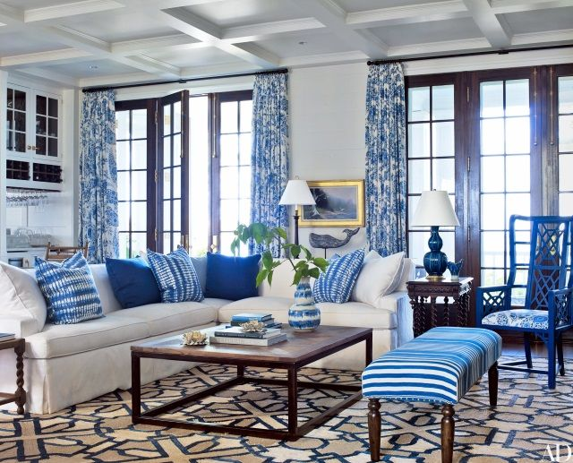 A cobalt blue and cream geometric rug adds energy and pulls together blue and white fabrics in the living room of a house in Port Clyde, Maine by designer Suzanne Kasler and architect Les Cole.