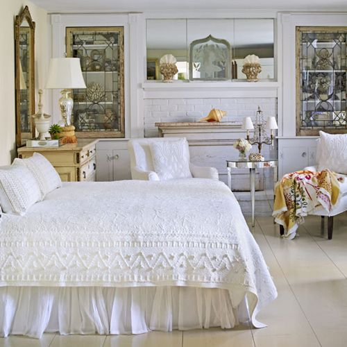 """""""Crisp white lace bedding, lighting fixtures with white shades, stained glass cabinet doors, and antique mirrors above a white fireplace"""