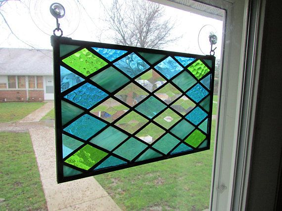 This stained glass panel is made with a diamond pattern. The center has 8 - 1 1/2x 2 1/2 clear diamond bevels in a diamond shape. The diamond cut glass is in differnent shades and textures of aqua and green glass. The border is a 1/4 zinc finished in a black patina. Measures