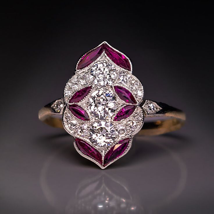 Antique Early Art Deco Diamond Ruby Engagement Ring, Austrian, Vienna, circa 1915. A delicate early Art Deco platinum topped 14K gold engagement ring is densely set with bright white old European cut diamonds accented by stylized ruby leaves.
