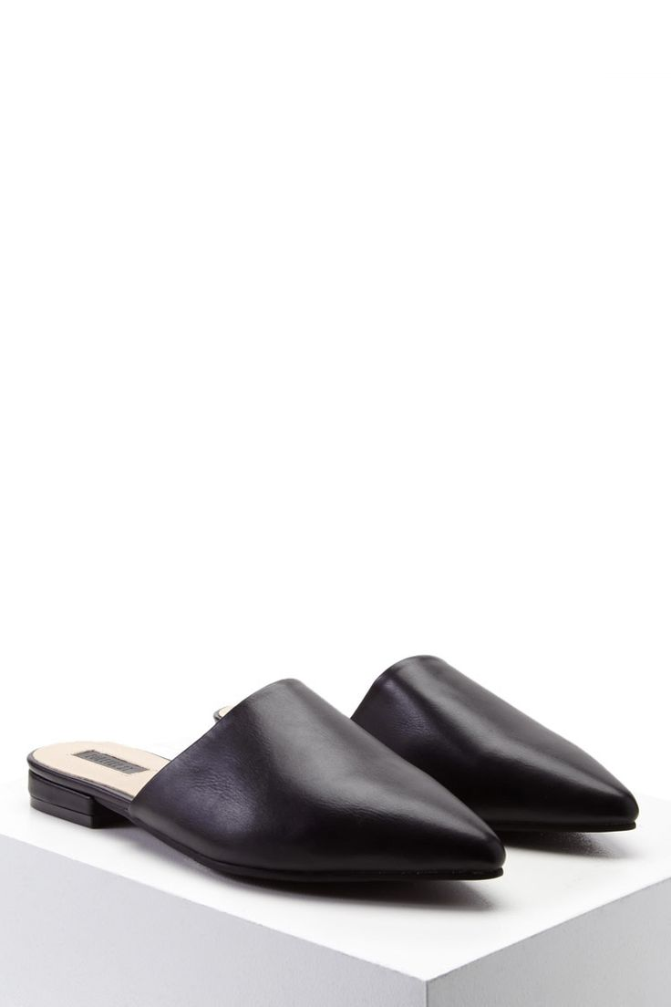 A pair of faux leather mules featuring a pointed toe, a low heel, and a slip-on style.