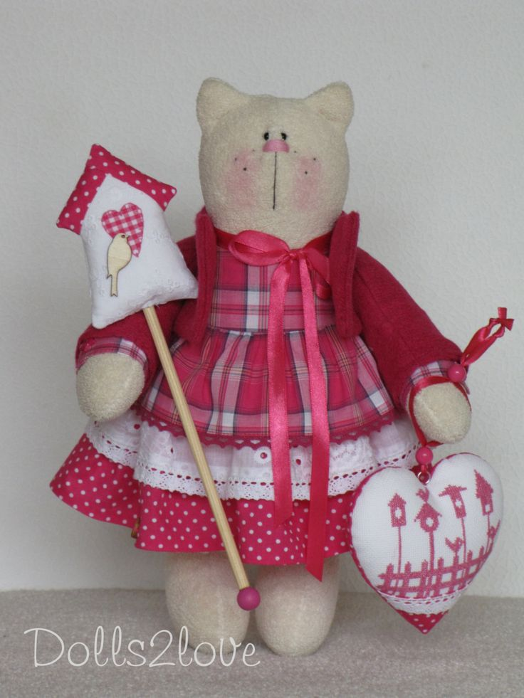 Tilda Cat Birdie wearing a pink polka dot and checkered dress and a pink jacket…