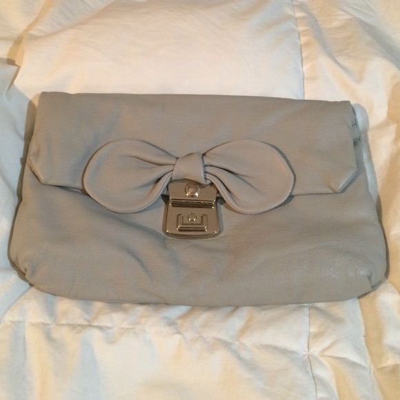 ‼️20% FOR 20 LIKES‼️ Marc by Marc Jacobs clutch Between the bow detail and the heart lining, this purse is enough to put a smile on any ones face! Girlie details with sophistication...smooth grey leather and silver details make this a must get! Can be worn two ways...as a clutch or a shoulder bag! Not a mark!! Marc by Marc Jacobs Bags Clutches & Wristlets