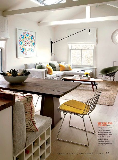 MAKE A SMALL SPACE FEEL LARGER with an open floor plan. Here, banquette seating allows for storage and a wine rack. White walls and windows installed on the ceiling brighten up the space.
