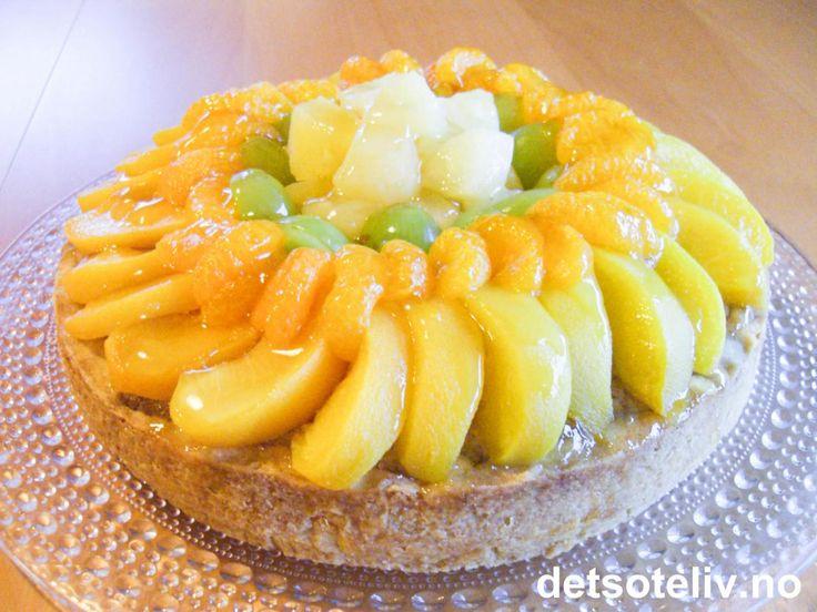 Myk og smakfull mandelkake som dekkes med hermetiske mandariner, hermetiske fersken, ananas og grønne druer. Frukten glaseres med smeltet eplegelé, hvilket gir hele kaken en vakker glans.