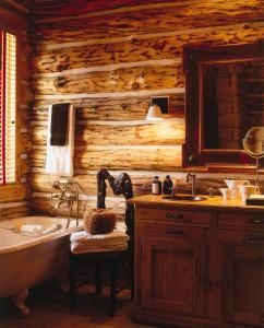 Exposed logs, warm tones of wood and a footed bathtub contribute to the old fashioned ambiance in this bathroom. The backrest of the antique chair was carved from a tree root.