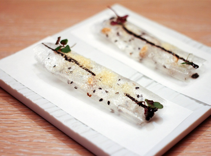 "Asian ""Coca de Vidrio"", translates to ""glass coconut"". Thin, glass-like flatbread represents melted crystallized sugar. This dish was created from a sheet of Japanese oblate paper, which is a clear, paper-thin edible paper made from potato starch, often used for packaging hard-to-swallow medicines. In this dish the obulate was made into a crispy roulade speckled with various Asian herbs and a strip of black sesame paste. Created by molecular gastronomy chef Jose Andres at his restaurant…"