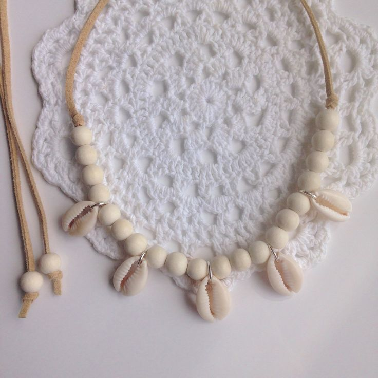 cowrie shell necklace off white wooden beads with beautiful cowrie shells on natural faux suede. can be worn long or as a choker necklace.