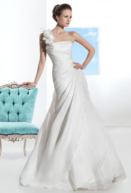 Brides: Demetrios - Illusions. Satin organza, A-line gown with flowers on one shoulder and asymmetrical pleating on bodice. Skirt features a side split with ruffles and attached chapel train. Available in white and ivory.