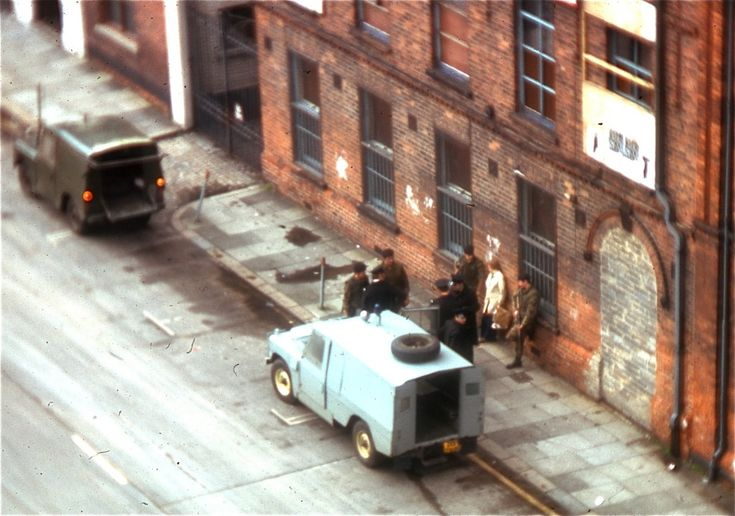 "1974: British troops interrogate a couple outside Belfast's Europa Hotel, which was known as the ""most bombed hotel in the world"" after suffering 28 bomb attacks during the Troubles. Photo: George Louis / Wikimedia"