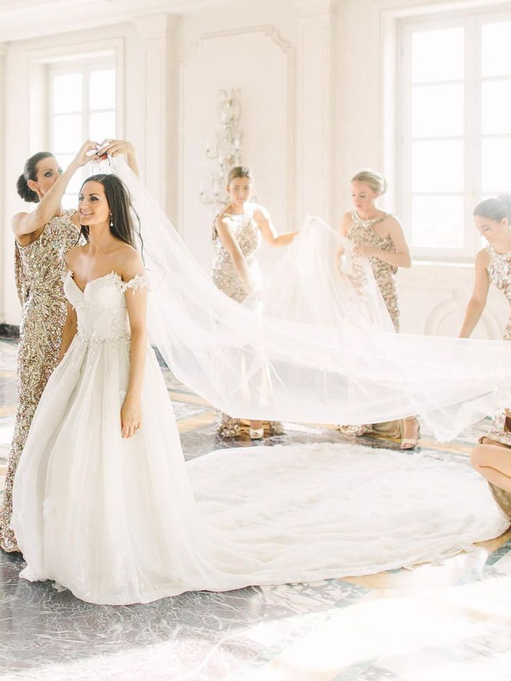 Take wedding photos by fashioning poses with the bride getting help from her bridesmaids before walking down the aisle.