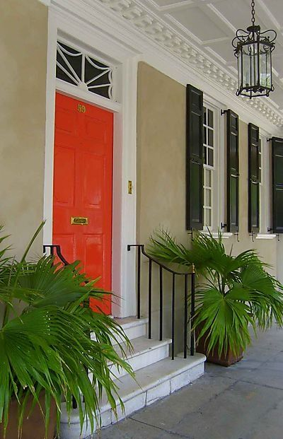 coral door, tan stucco, black shutters