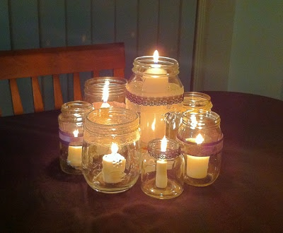Our DIY Centrepieces with the candles lit - old jars with ribbon & lace and all different size white candles (One Love, One Day: DIY Centrepieces)