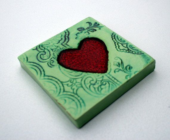 A very popular piece. A simple, elegant ceramic tile with a stunning red glaze heart at its center. The raw glaze is poured into the middle of