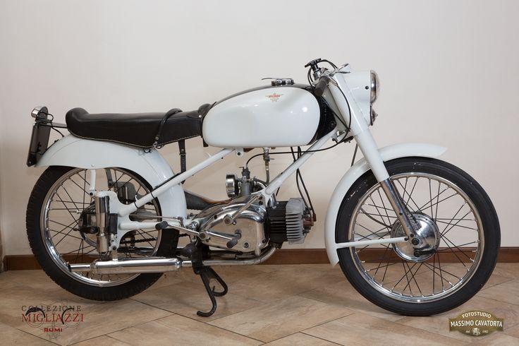 MOTO RUMI SPORT Nazione: Italia Tipologia: Sport Anno: 1954/1955 Tipo di motore: Bicilindrico a 2 tempi Cilindrata: 124,68 cc Potenza: 7 CV  Cambio: 4 marce Velocità massima: 100 Km/h Colore: Bianco con fascia nera sul serbatoio