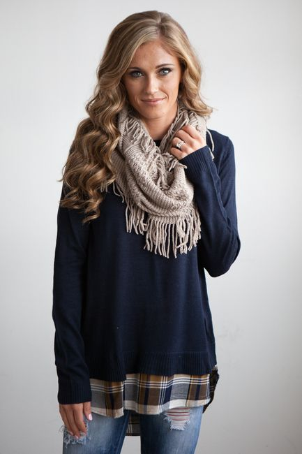 Cozy navy sweater with plaid hem and back detail.