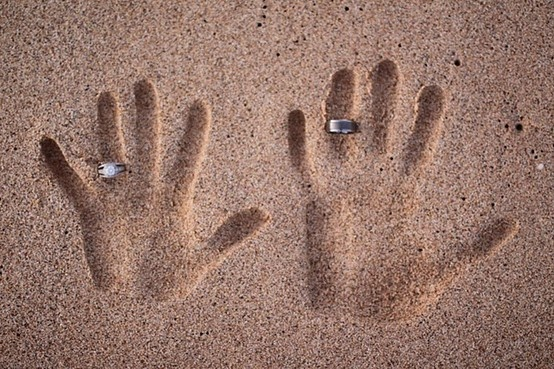 hands/rings in the sand, especially for a beach wedding