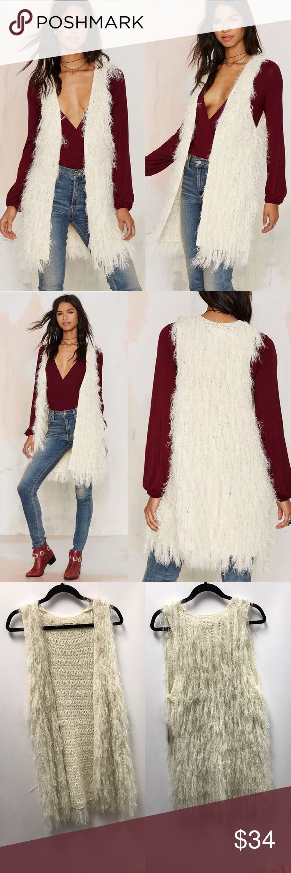 Faux Mo Shaggy Vest No mo FOMO. The Faux Mo Vest is made in an ivory knit and features shaggy faux fur detail, open front, and mid thigh length. Killer over a bell sleeve bodycon, or teamed up with a suede vest, chelsea boots, and the center of attention.  *Spandex/Acrylic  *Runs true to size  *Model is wearing size S/M  *Hand wash cold  *Imported cotton candy Sweaters