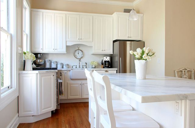 possibly white/grey streaked marble counters w/ simple white backsplash.