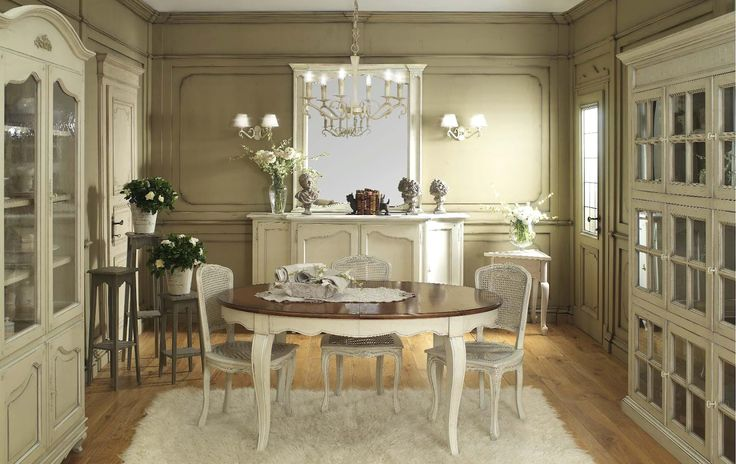 Interior Design Styles. Vintage French Shabby Chic Style Dining Room Design with Nice Classic Dishes and Cutlery Storage Cabinets, Round Dining Table with Lovely Dining Chairs and Beautiful White Fur Area Rug, Antique Cabinet with Big Wall Mirror and Decorations, and Gorgeous Classic-Style Chandelier and Wall Lamps. Uniquely Beautiful Shabby Chic Interior Design Style