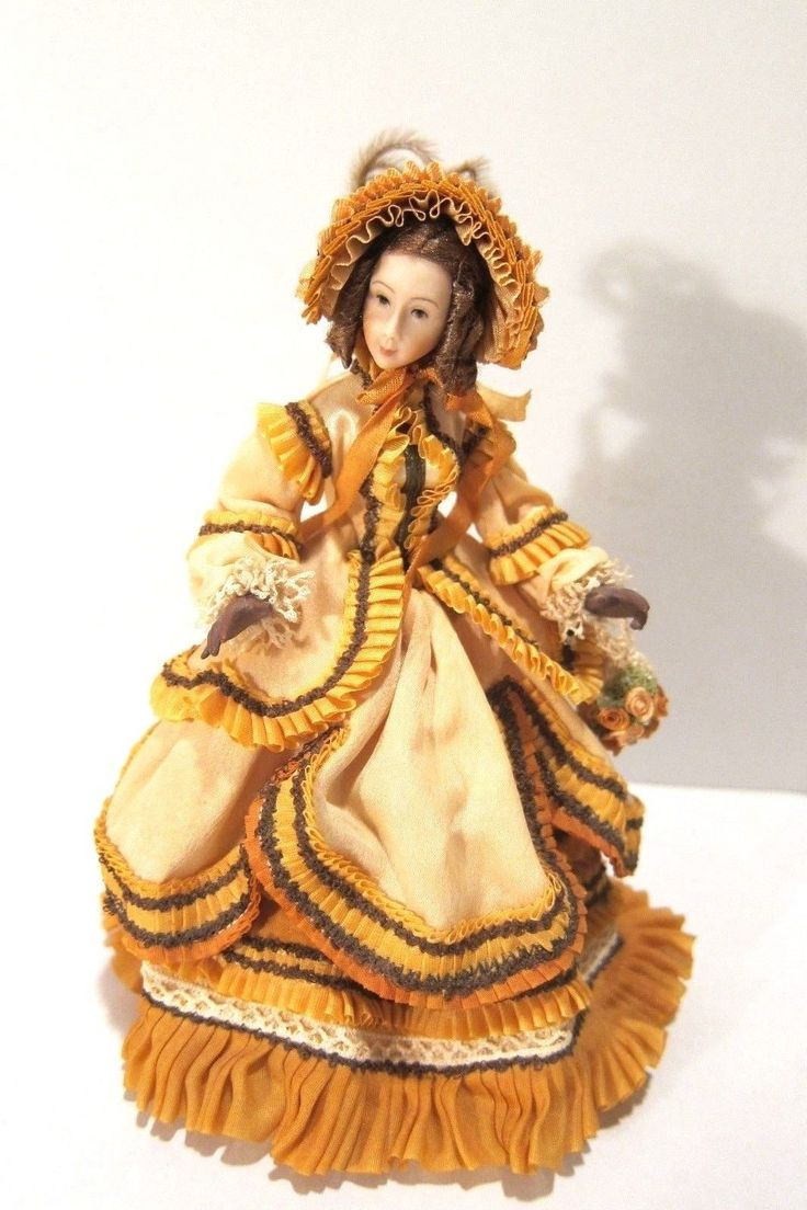 Stacey Hoffman - porcelain figure made from hand sculpted original molds; wearing a  pale rust dress adorned with lots of silk ruching in darker tones and brown. The hat is adorned with over a dozen silk roses and feathers and she has brown gloves (individual fingers} and carries a crocheted purse with roses. She is wearing high button shoes and her slip and pantaloons are the same color as the dress. Made in the early 1990s.