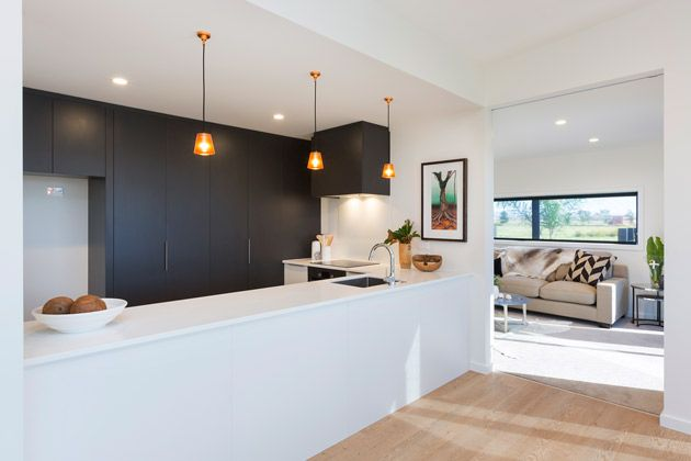 Bold dark grey cupboards contrasted with a white kitchen bench works well for this space. The pendulum lights really set it off. #ClassicBuilders #KitchenDesign