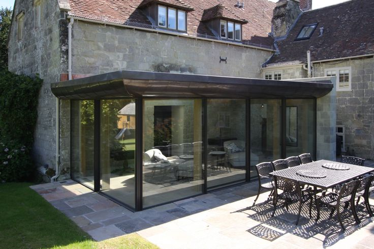 minimal windows sliding doors make up tow sides of the glass extension for a very frameless fully glazed structure www.iqglassuk.com