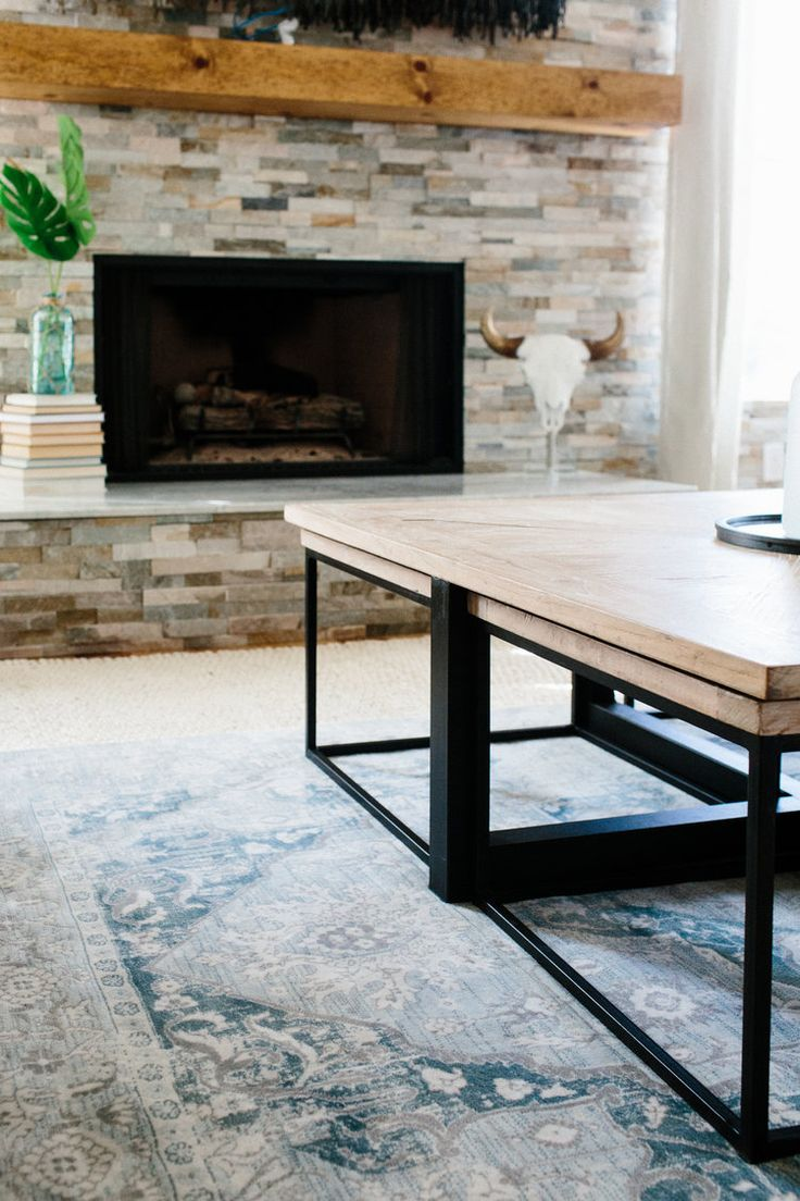 light wood and black iron modern coffee table with testing tables underneath and a blue oriental style rug