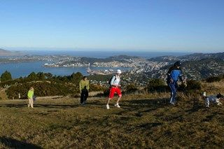 Family running up hill at Mount Kaukau, with city and sea in background.