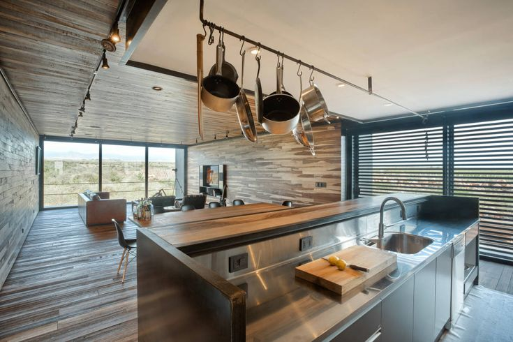 Beautiful, chic, modern, restaurant style with a touch of homeliness kitchen. Love the overhanging pots and pans, and the wooden feel of the whole room. By A4estudio