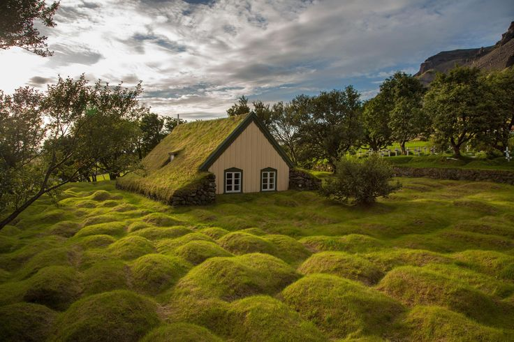 Hofskirkja Iceland - This picture taken in Iceland in the late afternoon. On the picture is a little church made from wood and peat (turf). Is one of the last peat churches in Iceland. The humps in the grass are ancient graves.  Photo by Menno Schaefer.
