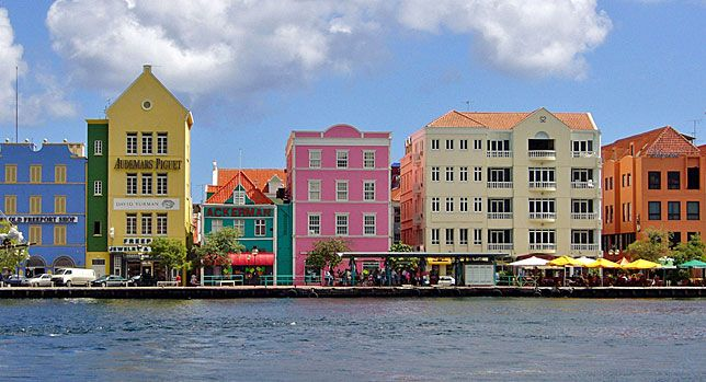 Willemstad, Curacao: Dutch-style buildings line the harbor at Willemstad, the capital city. Curacao is dry inland and has the same Dutch flavor as Aruba, and also lies off the Venezuela coast. Both islands have a population of ~150,000. Spanish, Dutch and English also are understood by virtually everyone.