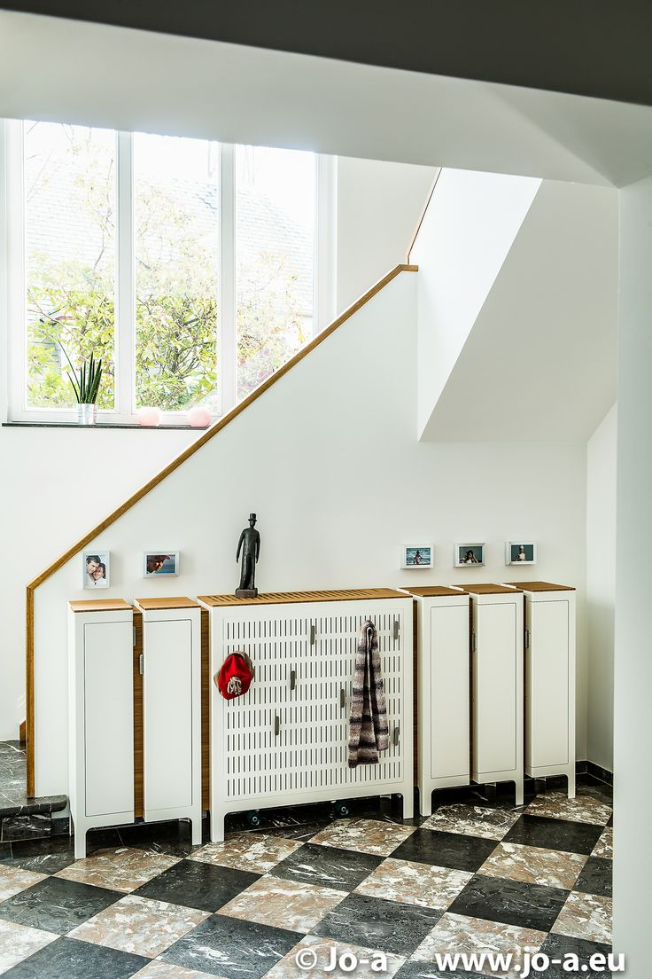 Casier storage unit installation in the hallway of a contemporary house in Brussels. Includes custom paneling to hide a conventional wall radiator.  #design #architecture #furniture