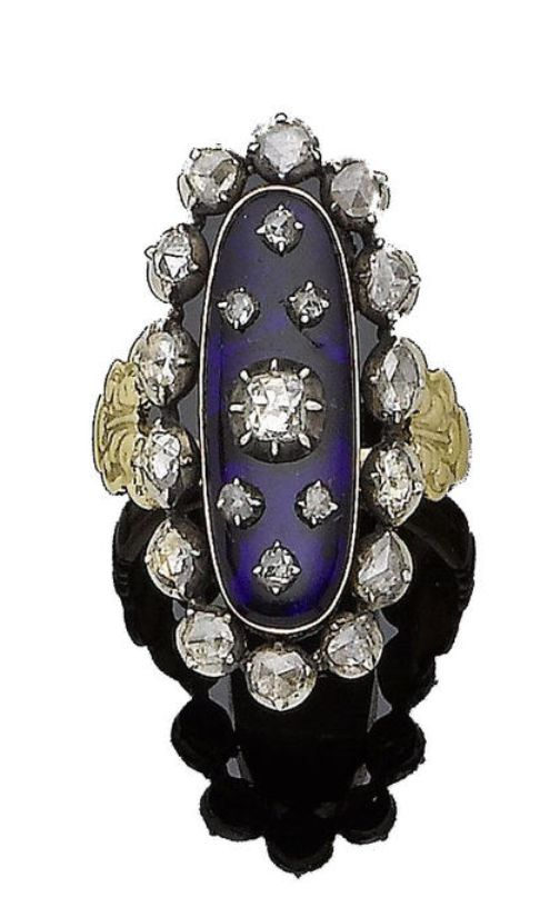 A late 18th century blue glass and diamond ring The elongated oval blue glass plaque applied with graduated rose-cut diamonds in pinched collet-setting, within a similarly-cut diamond surround, all in closed-back settings, between engraved shoulders of foliate design