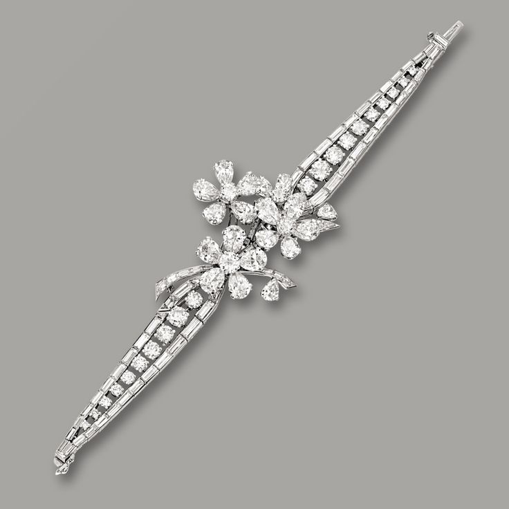 Diamond Bracelet, Van Cleef & Arpels The centre designed as three flowerheads, completed by a tapered strap set with brilliant-cut and baguette diamonds together weighing approximately 16.00 carats, mounted in platinum, signed VCA and numbered G375,