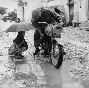 The British Army In Italy 1943, A little girl holding an umbrella watches a despatch rider attempt to clear the carbuerettor of his motorcycle in torrential rain, 4 October 1943. Pin by Paolo Marzioli