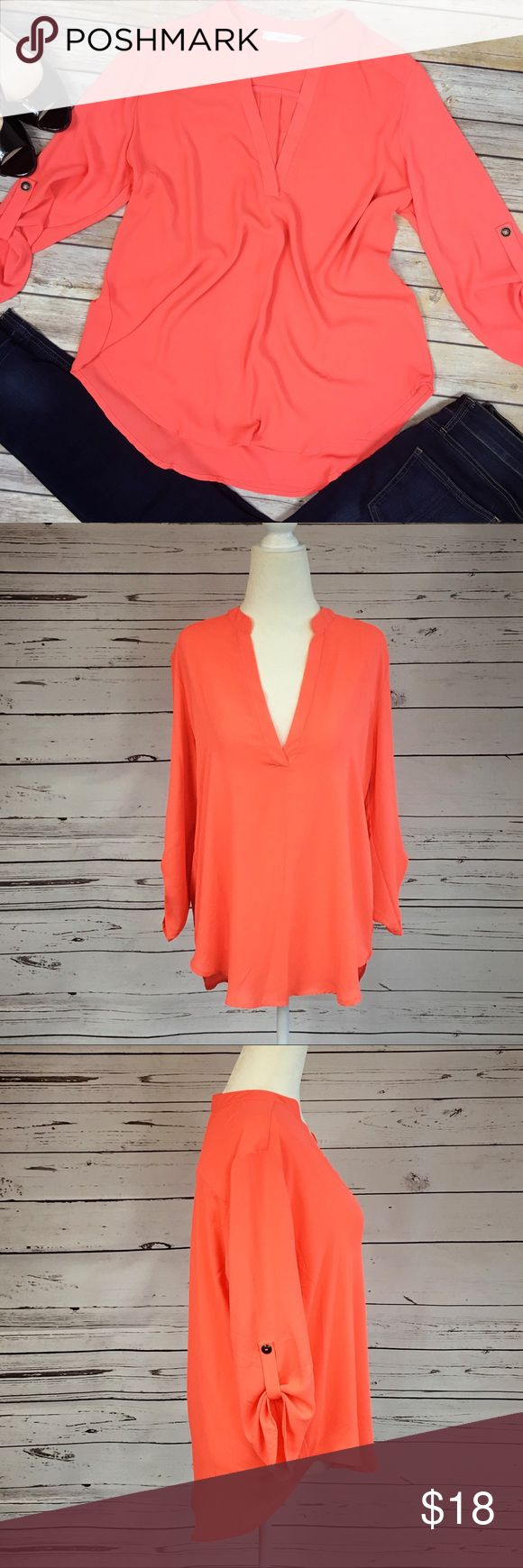 Lush High Low Coral Blouse Pretty coral blouse with button tab sleeves & High Low cut. Fabric content is 100 % polyester fabric has no stretch to it. Top of shoulder to bottom hem front side is approximately 25 1/2 inches, backside 28 1/2 inches, armpit to armpit is approximately 22 1/2 inches. Excellent used condition, no flaws. Color is best depicted in the first photo. Lush Tops Blouses