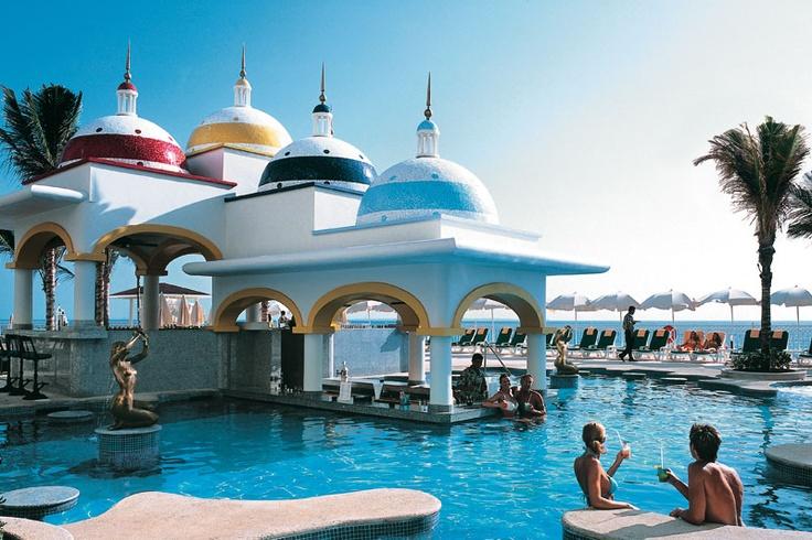 Se sitúa en la zona hotelera de Cancún, México, el Hotel Riu Caribe (Todo Incluido 24h) está a la orilla de una playa de aguas turquesas y arena fina. // Located in the hotel area of Cancún, Mexico, the Hotel Riu Caribe (All inclusive 24h) is the seaside of a beach with turquoise water and fine sand.