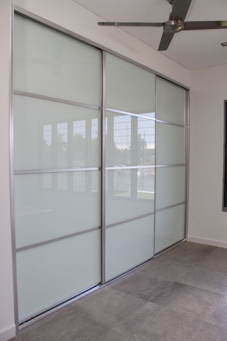 Four Panel Sliding Doors using white glass, bright silver frames. www.formfunctiont.com.au