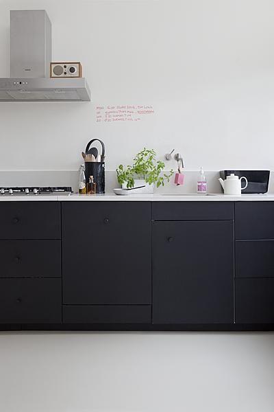 Keuken inspiratie | minimalistische strakke zwarte keuken fleur je op met bloemen | interieurinspiratie by www.vialin.nl